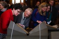 Symposium guests examining the Lectionaries side by side
